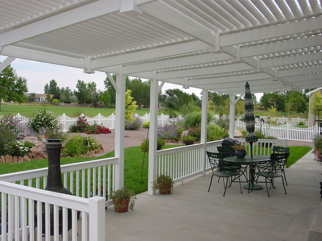 White vinyl pergola, patio railing and scalloped picket fence